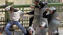 Police beat a protester during clashes in Cairo January 28, 2011. Police and demonstrators fought running battles on the streets of Cairo on Friday in a fourth day of unprecedented protests by tens of thousands of Egyptians demanding an end to President Hosni Mubarak's three-decade rule. (Amr Abdallah Dalsh/Reuters/Amr Abdallah Dalsh/Reuters)