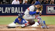 Toronto Blue Jays third baseman Josh Donaldson (left) scores the winning run past Texas Rangers catcher Jonathan Lucroy (right) in the 10th inning during game three of the 2016 ALDS playoff baseball series at Rogers Centre. (Nick Turchiaro/USA Today Sports)