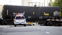 Local authorities sit trackside along a train derailment near the intersection of 15 St. and Blackfoot Trail S.E. in Calgary on Sept. 11, 2013. (CHRIS BOLIN FOR THE GLOBE AND MAIL)