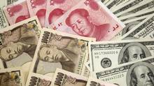 Japanese 10,000 yen notes, left, U.S. $100 notes, right, and Chinese 100 yuan notes, top. (TRUTH LEEM/REUTERS)