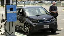 An attendee looks over a BMW i3 electric car at the Electric Power Research Institute's Plug-In 2014 conference in San Jose, Calif., on July 28, 2014. (ROBERT GALBRAITH/REUTERS)