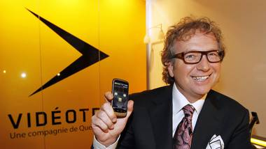 Videotron Ltee Chief Executive Robert Depatie holds a mobile phone at a news conference to launch the company's wireless network in Montreal, September 9, 2010.