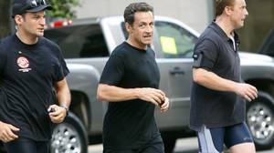 France's President Nicolas Sarkozy (C) is flanked by security officers after jogging in New York's Central Park in this July 17, 2009 file photo.