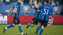 Montreal Impact's Justin Mapp, left, celebrates with teammates Davy Arnaud, centre, and Maxim Tissot after scoring against Toronto FC during first half second leg semifinal Amway Canadian Championship soccer action in Montreal, Wednesday, May 1, 2013. (Graham Hughes/THE CANADIAN PRESS)