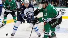 Winnipeg Jets' Jacob Trouba and Dallas Stars' Radek Faksa compete for control of the puck during a game in Dallas. Trouba has ended his holdout and signed a two-year deal to stay in Winnipeg. (Tony Gutierrez/The Canadian Press / AP)