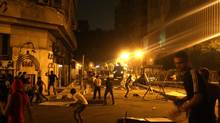 Protesters clash with police in front of the U.S. embassy in Cairo early Thursday. (MOHAMMED ABU ZAID/ASSOCIATED PRESS)