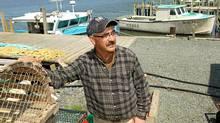 Fisherman Lloyd Robicheau next to his boat , Kyle Douglas, (L) at Fisherman's Reserve, Nova Scotia, May 18 , 2012. (PAUL DARROW/GLOBE AND MAIL)