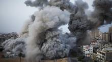 Israeli forces strike in Gaza City on Sunday, the deadliest day since the assault on Hamas officials began last week. (Bernat Armangue/Associated Press)