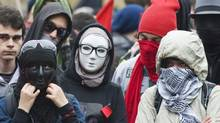 Masked protesters take part in an anti-capitalist demonstration in Montreal, Tuesday, May 1, 2012. Conservative MPs have agreed to impose a maximum 10-year prison term on protesters who wear masks while inciting a riot, and lesser sentences and fines for the mere act of being present at a riot in a mask. (CP)