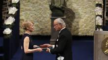 Jenny Munro, daughter of the 2013 Nobel Prize Laureate in Literature Alice Munroe of Canada, receives the Nobel Prize in her place from Sweden's King Carl XVI Gustaf, during the Nobel Prize award ceremony at the Stockholm Concert Hall in Stockholm, Tuesday, Dec. 10, 2013. The Nobel awards are always awarded on Dec. 10, the anniversary of Alfred Nobel's death in 1896. The prizes for laureates in medicine, chemistry, physics, economics and literature are awarded in the Swedish capital Stockholm, whilst the Nobel Peace Prize is awarded on the same day in Oslo, Norway. (Frank Augstein/AP Photo)