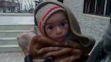A toddler is held up to the camera in this still image taken from video said to be shot in Madaya on January 5, 2016. Warnings of widespread starvation are growing as pro-government forces besiege an opposition-held town in Syria and winter bites, darkening the already bleak outlook for peace talks the United Nations hopes to convene this month (Handout/Reuters)