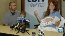 Amber Miller, of Westchester, Ill., gestures during a news conference as she holds her baby at Central DuPage Hospital in Winfield, Ill., Monday Oct. 10, 2011. (Mark Black/Mark Black/AP Photo/Daily Herald)