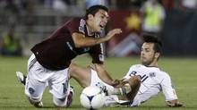 Colorado Rapids midfielder Martin Rivero, left, falls after running into Vancouver Whitecaps midfielder Davide Chiumiento and losing the ball in the second half of the Whitecaps' 1-0 victory in a Major League Soccer game on Wednesday, July 4, 2012, in Commerce City, Colo. (David Zalubowski/AP)