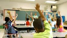 Children in a classroom responding to the teacher's question. (Nancy Louie/iStockphoto)