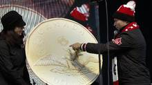 Steve Podborski, right, Chef de Mission for Canada at the 2014 Winter Olympics, inspects the newly unveiled 'Lucky loonie' during a send-off party for Canada's Sochi bound Olympic athletes in Banff, Alta., Saturday, Jan. 11, 2014. (Jeff McIntosh/The Canadian Press)