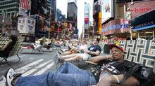 Michael Johnson takes a break on a lounge chair in the middle of Broadway in New York's Times Square. Sections of Broadway that run through Times Square and Herald Square have been closed to cars in an effort to reduce traffic and pollution, and cut down on pedestrian accidents. (Seth Wenig/The Associated Press/Seth Wenig/The Associated Press)