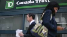 People walk past a Toronto-Dominion Bank branch in Ottawa (CHRIS WATTIE/REUTERS)