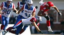 Montreal Alouettes' Michael Klassen, left to right, Shea Emry, and Chip Cox, send Calgary Stampeders' Jon Cornish, flying during first half CFL action in Calgary, Alta., Saturday, July 20, 2013. (Jeff McIntosh/THE CANADIAN PRESS)