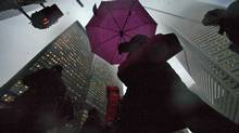 People walk through a foggy scene on Bay Street in the financial district in Toronto on Feb. 18, 2009. (MARK BLINCH/Mark Blinch/Reuters)
