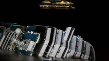 The cruise ship Costa Serena passes offshore as its sister ship, Costa Concordia, lies on its side off the tiny Tuscan island of Giglio, Italy, on Wednesday. (Angelo Carconi/AP/Angelo Carconi/AP)