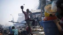 A Morsi supporter runs away from security forces who fired on protesters in the Nasr City sit-in. Egyptian police in riot gear swept in with armoured vehicles and bulldozers to clear two sprawling encampments. (Manu Brabo/Associated Press)