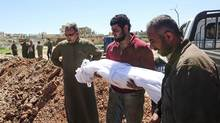 Syrians bury the bodies of victims of a a suspected toxic gas attack in Khan Sheikhun, a nearby rebel-held town in Syrias northwestern Idlib province, on April 5, 2017. International outrage is mounting over a suspected chemical attack that killed scores of civilians in Khan Sheikhun on April 4, 2017. (FADI AL-HALABI/AFP/Getty Images)