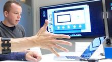 Stephen Lake, CEO and co-founder of Thalmic Labs, helps demonstrate the company's Myo armband device at his office in Kitchener, Ont. (Patrick Dell/The Globe and Mail)