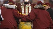 Washington Redskins starting quarterback Robert Griffin III is helped off the field (GARY CAMERON/REUTERS)