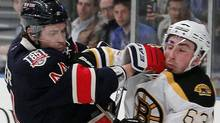 New York Rangers' Steve Eminger (44) is checked by Boston Bruins' Brad Marchand (63) during the first period of an NHL hockey game at Madison Square Garden, in New York, Monday, April 4, 2011. (AP Photo/Paul J. Bereswill) (Paul J. Bereswill/AP)