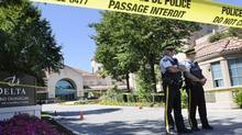 RCMP members guard the scene at the Delta Grand Hotel in Kelowna, B.C., on Tuesday, Aug. 16, 2011 where a brazen gangland-style shooting took place. (The Canadian Press/GARY NYLANDER/The Canadian Press/GARY NYLANDER)