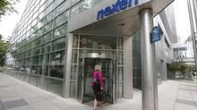 A woman walks into the Nexen building in downtown Calgary, Alberta, July 23, 2012. China may soon get control of a large slice of UK North Sea oil supply, which is key to determining global oil prices, if bids by its state firms for assets of Canadian oil companies Nexen and Talisman are cleared by the regulators. (TODD KOROL/Reuters)