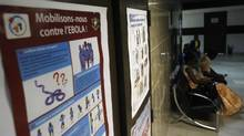People sit near a poster with a government message against Ebola, at the health minister's office in Abidjan August 11, 2014. (Luc Gnago/Reuters)