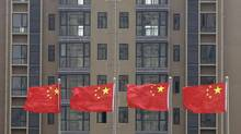 Chinese national flags fly in front of a newly-built residential apartment in Wuhan, Hubei province July 10, 2012. (DARLEY SHEN/REUTERS)