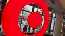 An employee at the new CityTarget store sits in a store window overlooking downtown Chicago, as they prepare for the opening, July 18, 2012. (JIM YOUNG/REUTERS)