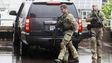 Armed officers jump out of a truck as it escorts the van transporting Justin Bourque to the courthouse in Moncton, New Brunswick June 6, 2014. Canadian police have arrested Bourque, 24, suspected of having shot dead three police officers and wounding two more, ending a massive manhunt, the police said on Friday. The shooting in the eastern city of Moncton was one of the worst of its kind in Canada, where gun laws are stricter than in the United States and deadly attacks on police are rare.