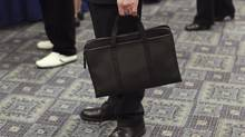 A man holds his briefcase at a job fair in New York April 18, 2012. (© Shannon Stapleton / Reuters/REUTERS)