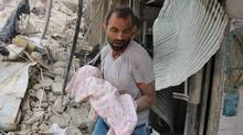 A Syrian man carries the body of an infant retrieved from under the rubble of a building following a reported airstrike on September 23, 2016, on the al-Muasalat area in the northern Syrian city of Aleppo. (THAER MOHAMMED/AFP/Getty Images)