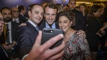 Emmanuel Macron (center), candidate for the 2017 French presidential elections, takes selfies with guests during the annual dinner of the Representative Council of France's Jewish Associations (CRIF) in Paris, on Feb. 22, 2017. (Christophe Petit Tesson/Pool via AP)