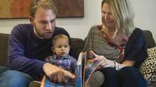 Bojan Djuricic, left, and his wife Naomi Sutorius-Lavoie, right, read a Serbian book to their daughter Mila Sutorius- Djuricic in Toronto on Wednesday, Oct. 17, 2012. Djuricic will be taught to speak in English, French and Serbian. (Nathan Denette/THE CANADIAN PRESS)