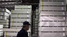 A man walks past a stack of drywall at an Ohio factory in 2012. The federal government is moving up a review of preliminary anti-dumping duties imposed on drywall imports into Canada. (Jae C. Hong/The Associated Press)