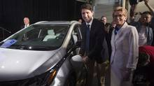 Prime Minister Justin Trudeau, left, and Ontario Premier Kathleen Wynne pose as they plug in an electric vehicle at the General Motors plant in Oshawa, Ont., in a June 10, 2016, file photo. (Chris Young/THE CANADIAN PRESS)