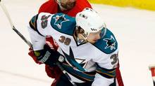 Detroit Red Wings defenseman Brad Stuart (23) checks San Jose Sharks center Logan Couture (39) as goalie Jimmy Howard (35) makes a save in the first period during Game 6 of the NHL Western Conference semi-final hockey playoff in Detroit, Michigan May 10, 2011. (Rebecca Cook/Reuters)