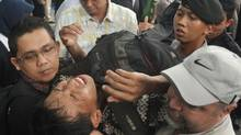 This file photo taken on November 25, 2011 shows security personnel evacuating a man after he collapsed while queueing for discounted BlackBerry smart phones at a mall in Jakarta. On December 5, 2011 Indonesian police named Research In Motion's country director a suspect for negligence after a BlackBerry promotion turned chaotic and left dozens injured and others knocked unconscious. Andrew Cobham, president director for Research in Motion (RIM) in Indonesia, and British security consultant Terry Burkey were named as two of four suspects in the incident at a Jakarta mall and could face five years' imprisonment. (DANNY/AFP/Getty Images/DANNY/AFP/Getty Images)