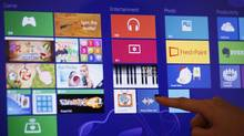 An attendant demonstrates the Microsoft Windows 8 operating system during its launching ceremony in Hong Kong Friday, Oct. 26, 2012. Microsoft launched a radical redesign of its world-dominating Windows operating system, introducing a touch-enabled interface that attempts to bridge the gap between personal computers and fast-growing mobile devices powered by the company's fiercest competitors. (Kin Cheung/AP)
