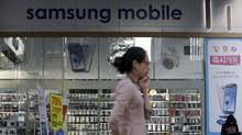 A woman walks past banners advertising Samsung smartphones at a mobile phone shop in Seoul, South Korea, Oct. 2, 2012. South Korea's Samsung Electronics Co. says it has filed a motion Monday with the California court to add Apple's iPhone 5 to their continuing patent battle. (Lee Jin-man/AP)