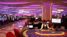A croupier sits at a baccarat gaming table inside a casino during the opening day of Sheraton Macao Hotel at the Sands Cotai Central in Macau Sept. 20, 2012. In the Philippines, the casino rush is starting with the slated opening in March of port magnate Enrique Razon Jr.'s $1.2-billion (U.S.) Solaire property. (Kin Cheung/AP)
