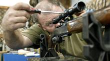 An Ottawa gun shop owner adjusts a scope on a rifle in December of 2002. (DAVE CHAN/Dave Chan/The Globe and Mail)