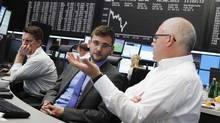 Traders work at their desks in front of the DAX board at Frankfurt's stock exchange June 18, 2012. (ALEX DOMANSKI/REUTERS)