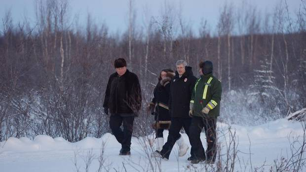 Prime Minister Stephen Harper and Northwest Territories Premier Bob McLeod, left, arrive outside Inuvik, Northwest Territories, on Wednesday to tour the site of an all-weather road linking Canada's Arctic coast to the south for the first time. (Jonathan Hayward/The Canadian Press)