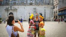 A tourist poses with two women clad in typical attires in a street of Old Havana, Cuba, on Sept. 18. The tourists keep visiting Cuba, but infrastructure is bursting at the seams. (YAMIL LAGE/AFP/Getty Images)